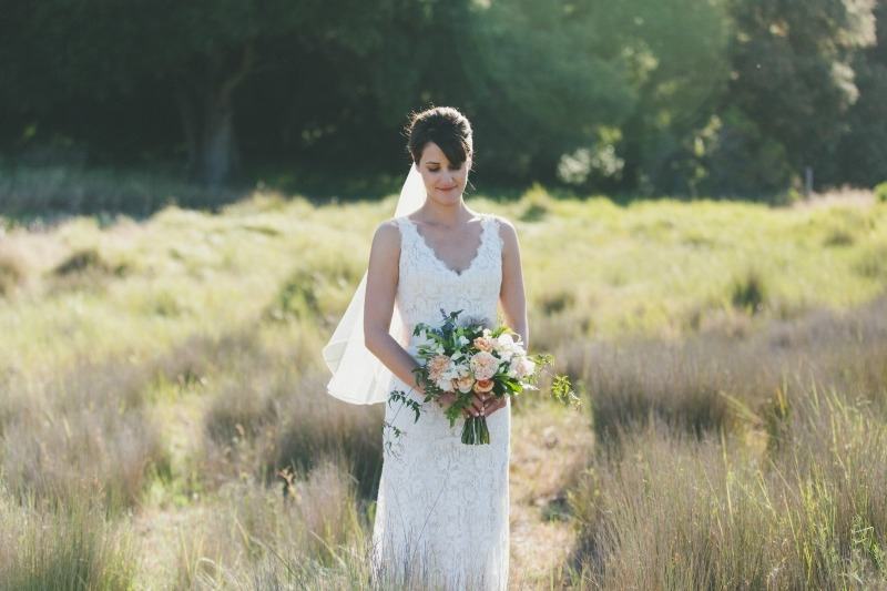 The glowing bride standing in the field of summer grasses. Flowers by Seascape Flowers. Coordinated by Coastside Couture. Photography by Two Foxes Photography. Location at the Santa Lucia Preserve.