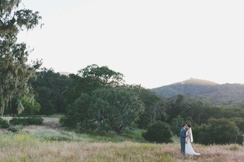 The bride and groom standing in the midst of breathtaking vistas. Flowers by Seascape Flowers. Coordinated by Coastside Couture. Photography by Two Foxes Photography. Location at the Santa Lucia Preserve.