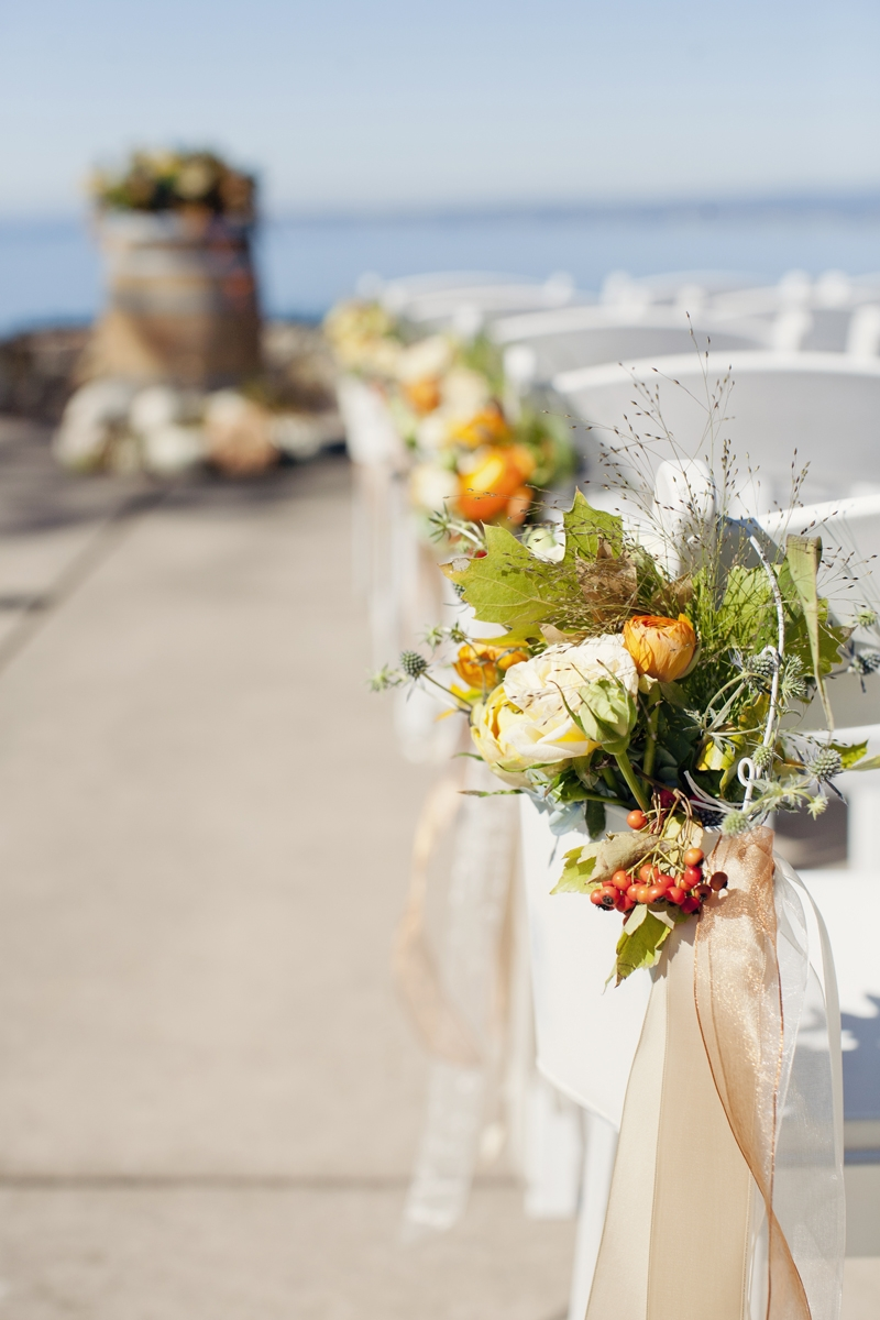 White wash metal pockets filled with flowers hanging from chairs  are a whimsical touch to this fall wedding. Flowers and Decor by Seascape Flowers. Photography by  Evynn Levalley Photography. Linens by La Tavola Linens. Venue at Seascape Beach Resor