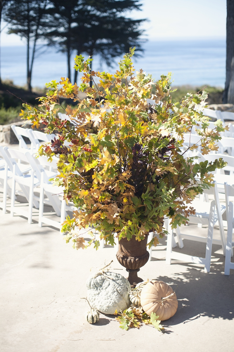Rustic fall urns with piles of heirloom pumpkins make for a whimsical detail at the back of the aisle. Flowers and Decor by Seascape Flowers. Photography by  Evynn Levalley Photography. Linens by La Tavola Linens. Venue at Seascape Beach Resort.