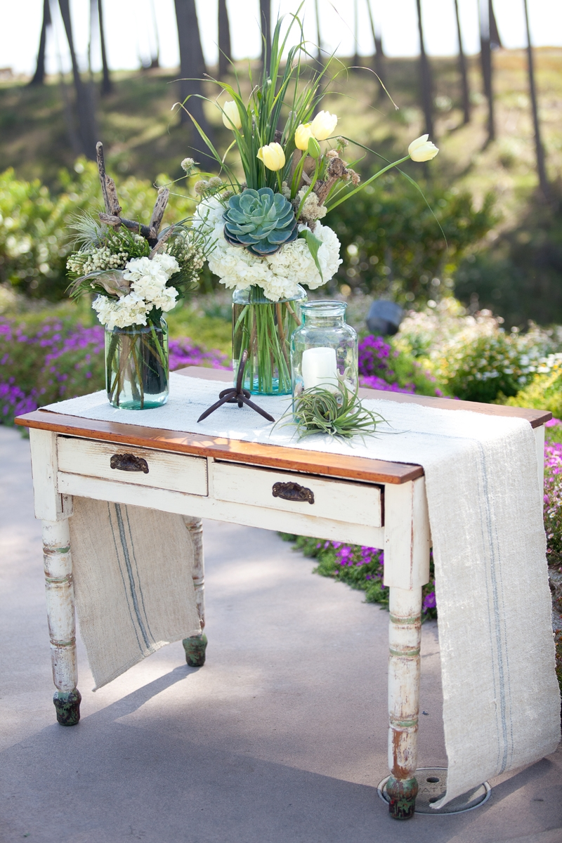 This vintage sign in table is styled to perfection! Flowers and decor by Seascape Flowers. Photographed by Danielle Gillet Photography. Linens by La Tavola Linens. Venue at Seascape Beach Resort.