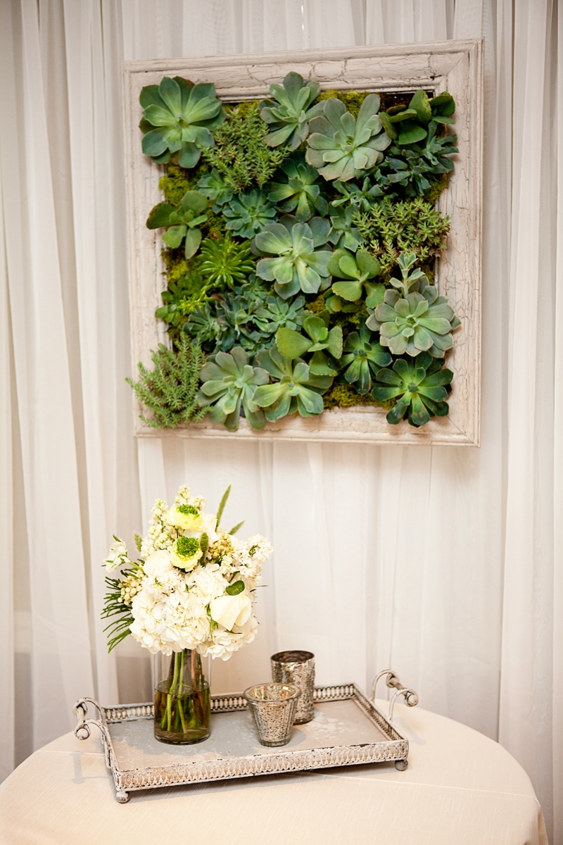 The guest book table is accented with this incredible hanging succulent garden. Flowers and decor by Seascape Flowers. Photographed by Danielle Gillet Photography. Linens by La Tavola Linens. Venue at Seascape Beach Resort.