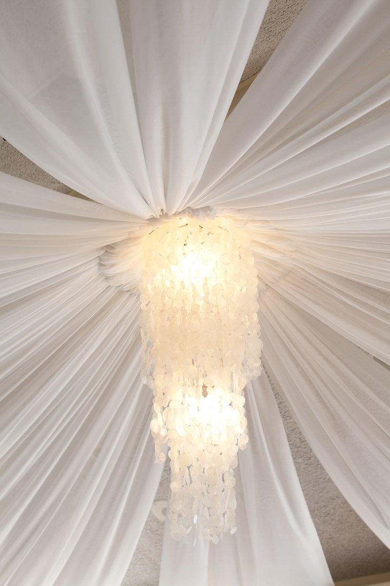 Love how dramatic this Capiz Shell Chandelier is! Flowers and decor by Seascape Flowers. Photographed by Danielle Gillet Photography. Linens by La Tavola Linens. Venue at Seascape Beach Resort.