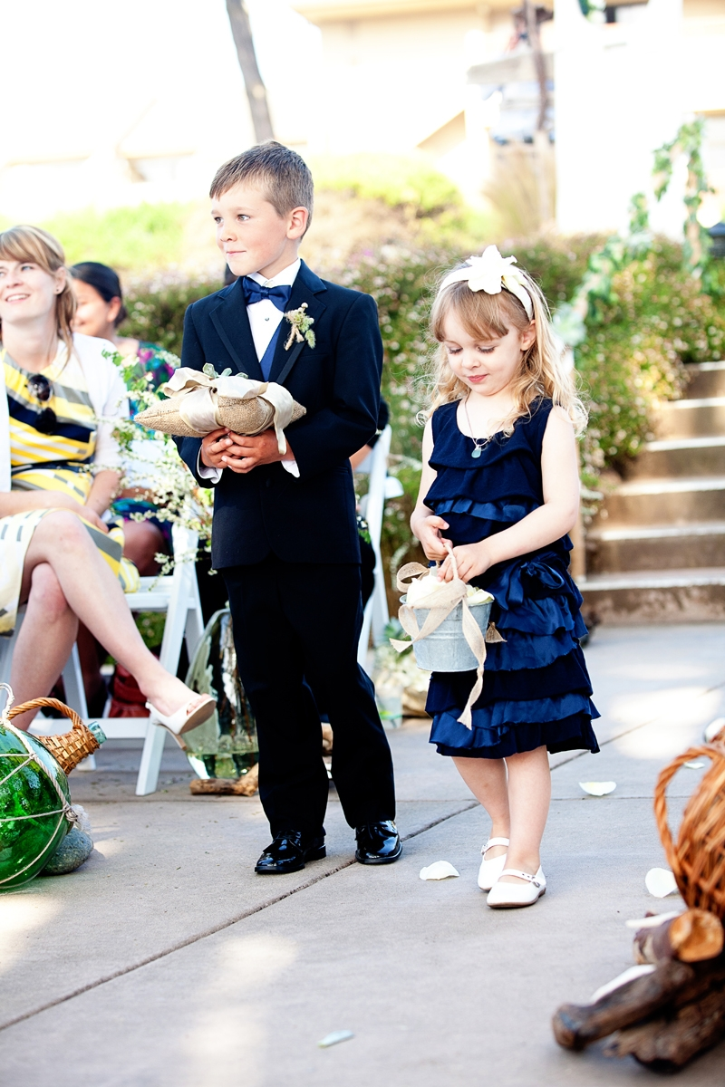 The ring bearer and flower girl make their way down the aisle. Flowers and decor by Seascape Flowers. Photographed by Danielle Gillet Photography. Linens by La Tavola Linens. Venue at Seascape Beach Resort.