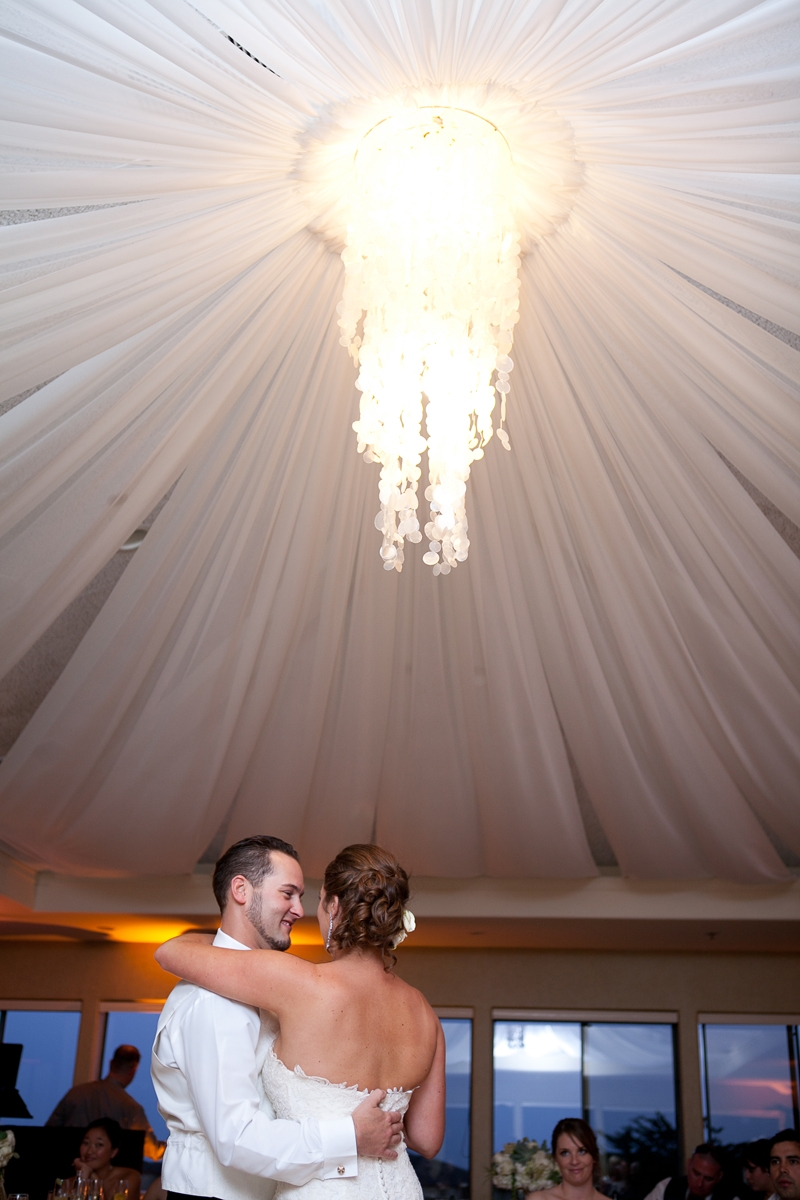 The happy couple take their first dance. Flowers and decor by Seascape Flowers. Photographed by Danielle Gillet Photography. Linens by La Tavola Linens. Venue at Seascape Beach Resort.