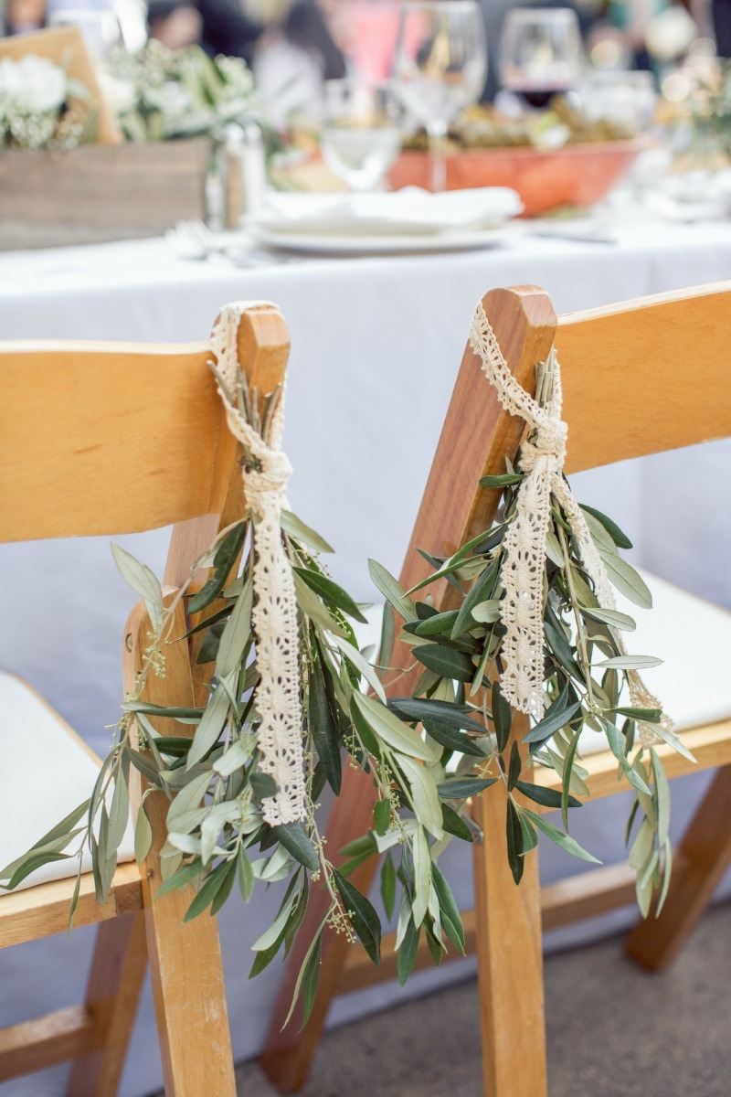 Olive branches helped decorated the bride and grooms chairs. Casual Holman Ranch Wedding. Flowers by Seascape Flowers. Coordinated by Coastside Couture. Photograhed by Carlie Statsky Photography. Paper Goods by Crescent Moon Paper. Catered by Paradis