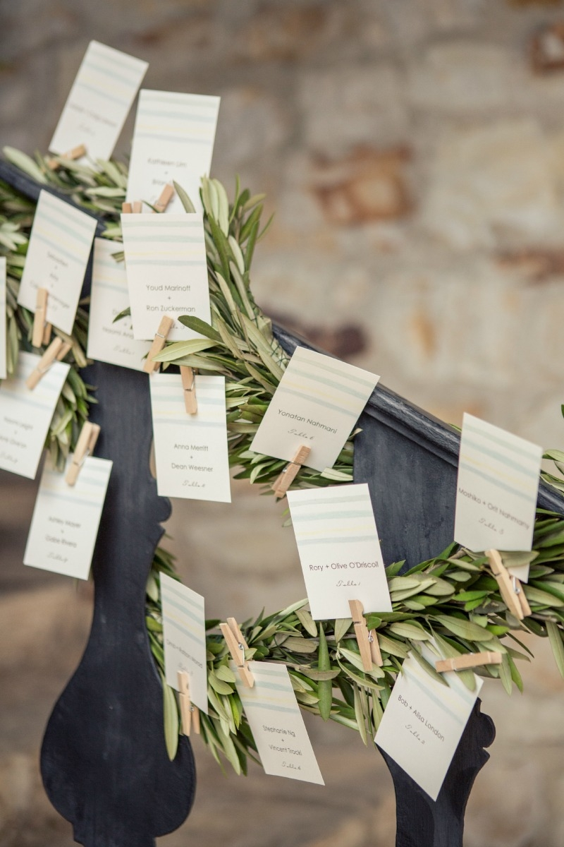 I love how the place cards were attached to olive garlands. Casual Holman Ranch Wedding. Flowers by Seascape Flowers. Coordinated by Coastside Couture. Photograhed by Carlie Statsky Photography. Paper Goods by Crescent Moon Paper. Catered by Paradise