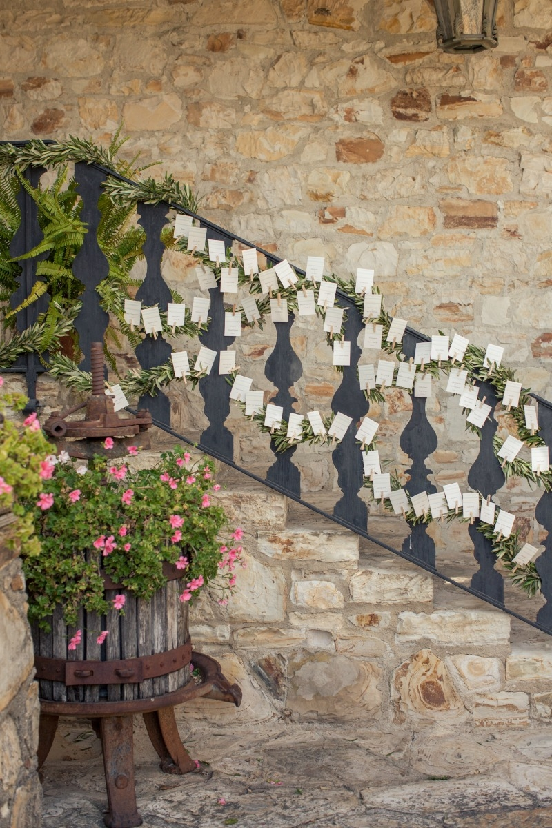 I love how the place cards were attached onto olive garlands. Casual Holman Ranch Wedding. Flowers by Seascape Flowers. Coordinated by Coastside Couture. Photograhed by Carlie Statsky Photography. Paper Goods by Crescent Moon Paper. Catered by Paradi