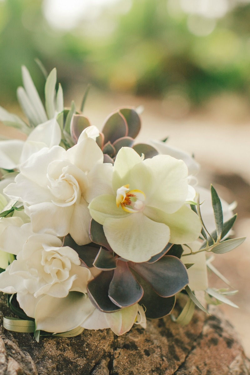 Love this orchid, succulent, gardenia, and olive bridal bouquet. Flower by Seascape Flowers. Coordinated by Coastside Couture. Photographed by Carlie Stasky Photography. Catering by A Taste of Elegance. Rentals from Classic Rentals. Tent from Chic Re