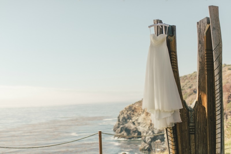 The brides gown floating above the sea. Flower by Seascape Flowers. Coordinated by Coastside Couture. Photographed by Carlie Stasky Photography. Catering by A Taste of Elegance. Rentals from Classic Rentals. Tent from Chic Rentals. Hair by Melissa Ma
