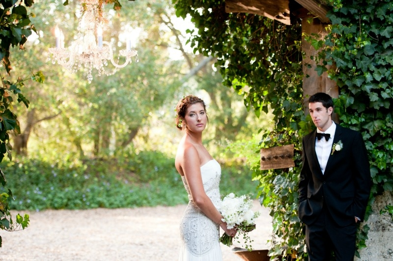 The bride and groom framed by the wine cellar doors at Sandrock Farms. Flowers by Seascape Flowers. Photography by Susannah Gill-Photographic Storytelling. Hair and make Up by Blending Beautiful. Dress from Jewels on Pacific Avenue. Cake by The Butte