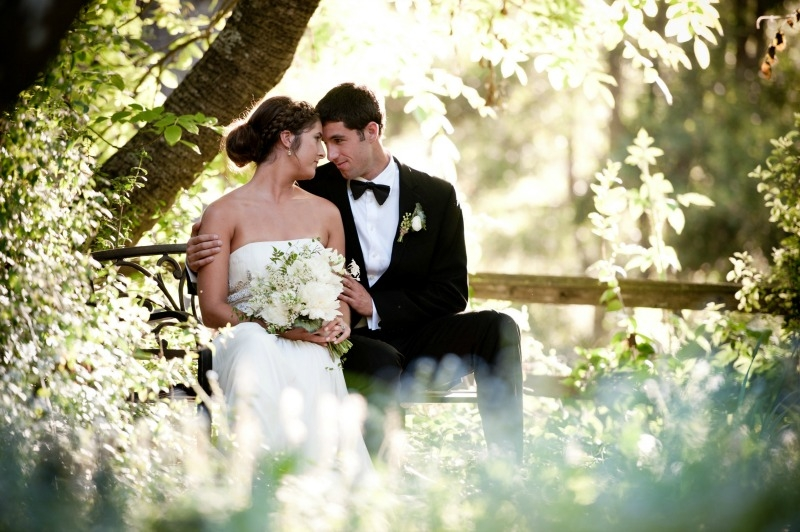 The bride and groom sitting on a park bench at Sandrock Farms. Flowers by Seascape Flowers. Photography by Susannah Gill-Photographic Storytelling. Hair and make Up by Blending Beautiful. Dress from Jewels on Pacific Avenue. Cake by The Buttery. Loca