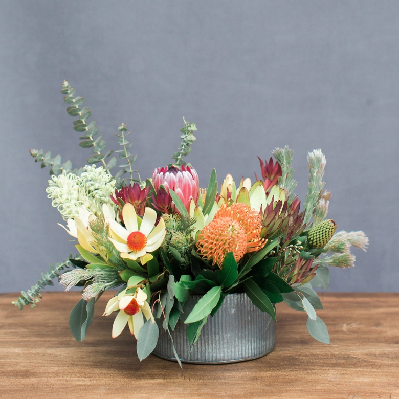 mixed locally grown protea in a low corragated metal container