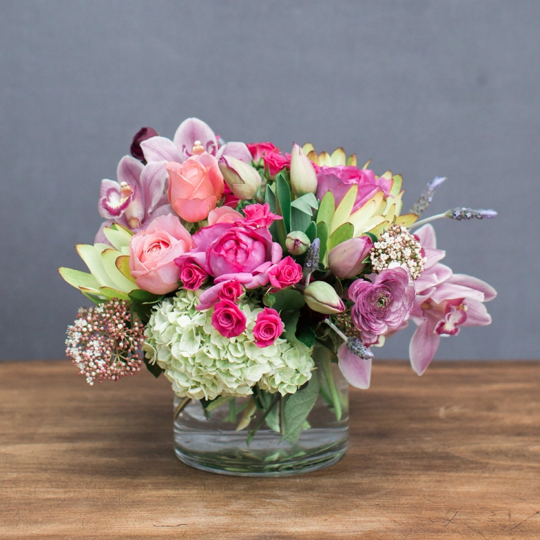 Low clear glass cylinder vase filled with brightly colored blooms brought in fresh fro the San Francisco Flower Market